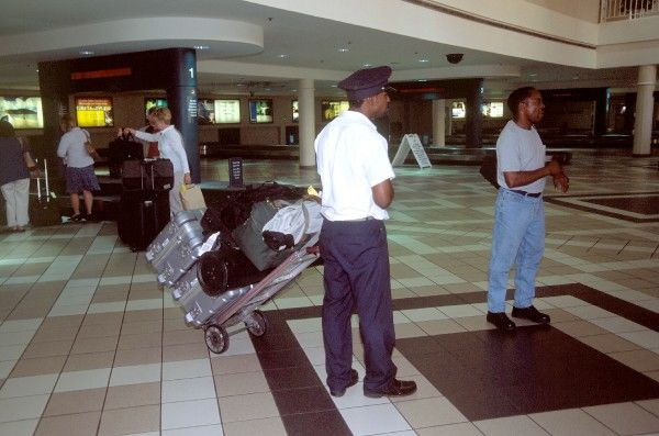Airport Porter USA. porter pulling trolley with cases birmingham alabama usa hobbs