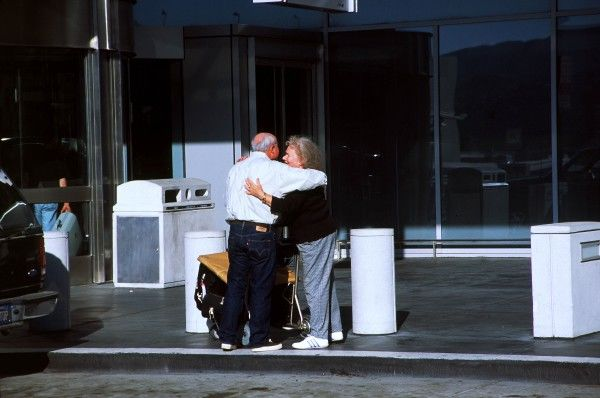 Arrivals Greeting. hugginh pax greeting or goodbye luggage rolley san fran hobbs