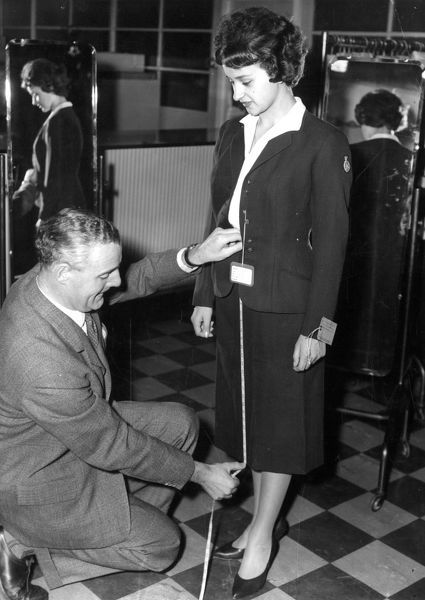 Maria Eugenia Ibarra is fitted out with an air hostess uniform by BOAC supplies officer.  Published December 23rd 1959