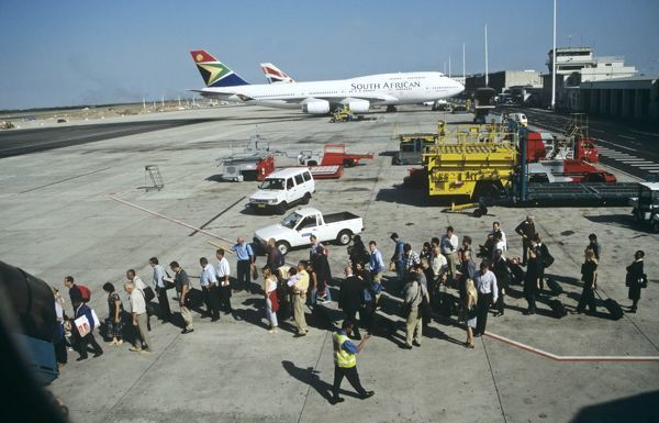 Passengers queue to board up steps at Jo'berg Airport South Africa