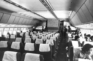 Airliner cabin in 1970s with passenger (front right) smoking on board